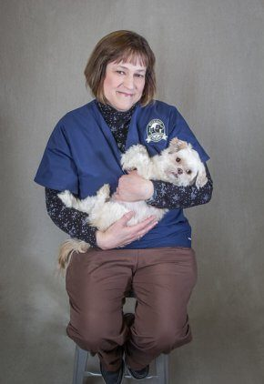 Dr. Laurie Sorrell-Raschi is board certified in veterinary anesthesia and analgesia. She is holding a cuddly white dog in her arms.