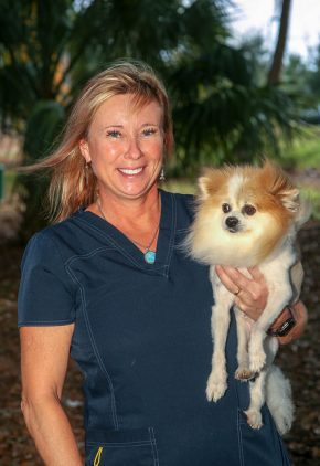 Dr. Helga Bleyaert is board certified in veterinary surgery. She is holding a small tan and white dog in her arms.