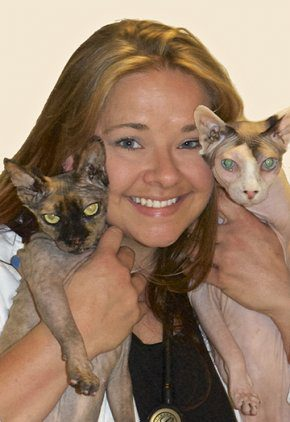 Dr. Meriam Molstad is an emergency medicine veterinarian. She is holding two hairless cats.