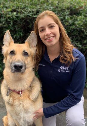 Dr. Lina Vaca is in our rehabilitation and acupuncture service. She is kneeling next to a large, long-haired dog.