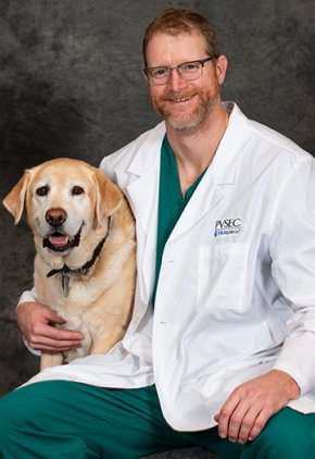 Dr. Jonathan Anderson is board certified in small animal surgery. Here he is with a blond Labrador retriever.