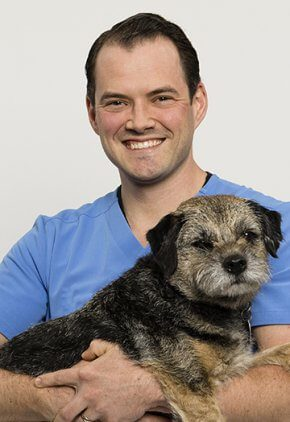 Dr. Patrick Kelly is an emergency medicine veterinarian. He is holding a wire haired dog.