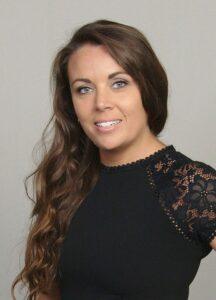 A brunette woman wearing a black shirt smiles.