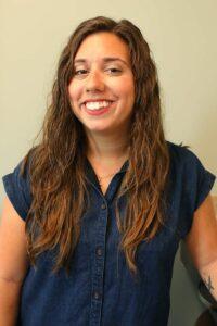 Smiling vet relations representative has long brown hair and wears a denim dress.
