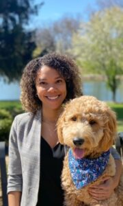 A brunette woman in a blazer poses with a goldendoodle