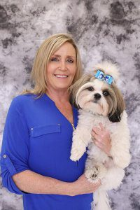 Blond woman with dark blue shirt on holds a fluffy white dog.