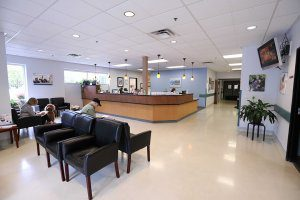 Bright spacious lobby with seating in forefront and help desk in background.