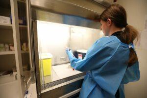 Female tech prepares chemo treatment behind glass hood.