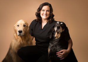A smiling brunette poses with her arms around two dogs.