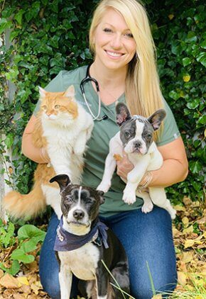 Dr. Brianna Miniter is a doctor in our surgery service. She is kneeling with a dog by her side and holding a dog and cat.
