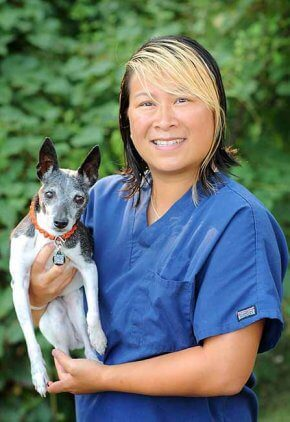 Melanie Tong is a certified veterinary technician with a specialty certification in anesthesia and pain management. She is holding a white and gray dog in her arms.