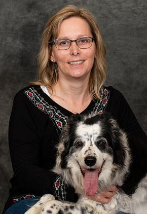 Vicky Miller is a Veterinary Technician Specialist (Anesthesia & Analgesia). She is holding a black and white dog.