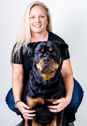 Dr. Tracey Rossi is board certified in veterinary internal medicine. Here she is with a black and brown dog.