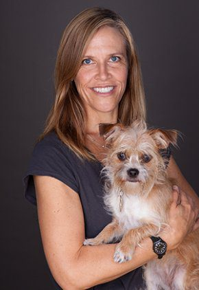 Dr. Erika Gebhard is a a doctor in our rehabilitation service. She is holding a brown and white wire-haired dog.