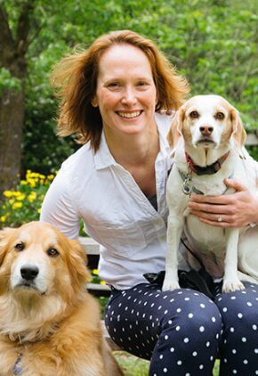 Dr. Laura Wilson is a board certified veterinary dermatologist. She is seen her with her two dogs, one on her lap and a larger one by her side.