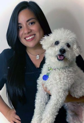 Dr. Barbara Avalos Cavero is an emergency medicine veterinarian. She is holding a white dog.