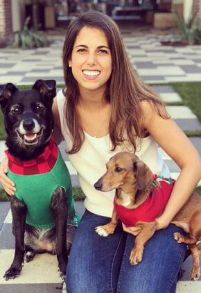 Dr. Hannah Klein is a small animal medicine and surgery intern. She is holding a dachshund wearing a red sweater on her lap and has her arm around a black dog wearing a green sweater and red checked scarf.