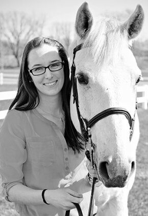 Dr. Brittney Stanton is a small animal medicine and surgery intern. She is with a white horse.