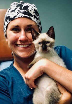 Dr. Madeleine Hendrix is a small animal medicine and surgery intern. She is in surgical cap and scrubs holding a cat.