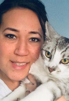 Dr. Michelle Yoshida is a small animal medicine and surgery intern. She is with a gray and white cat.