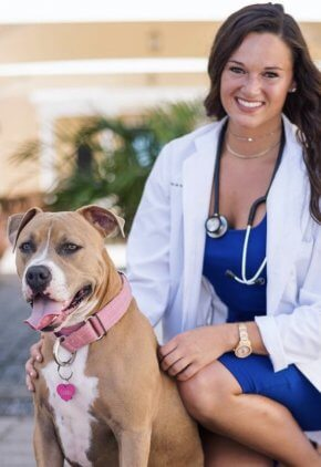 Dr. Tara Keaney is an emergency medicine veterinarian. She is kneeling next to a brown and white dog.