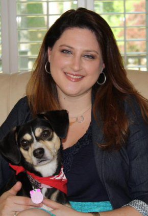 Dr. Dana Gale is a doctor in our emergency service. She is sitting with a mixed breed dog wearing a red scarf.