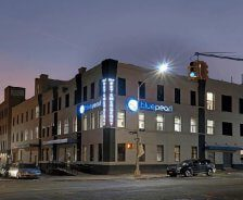 A BluePearl Pet Hospital has bright signs visible from a street at night.