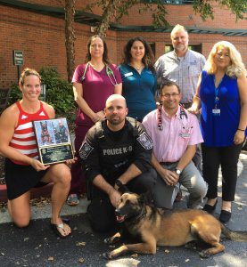 K9 Officer and handler give honorary plague to BluePearl Associates for exceptional care.