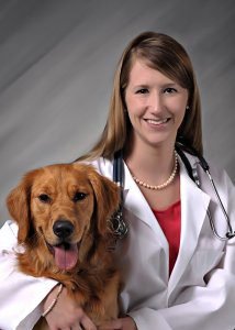 Female doctor with white coat with arm around dog.