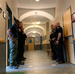 Officers wait in hallway of hospital.