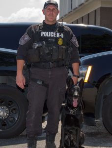 Police K9 handler poses proudly with black K9 officer.