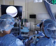 A team of surgeons use a scope to perform surgery.