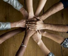 People huddle together with their hands in the center signaling teamwork.