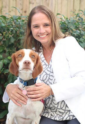 Dr. Jennifer Freeman is certified veterinary acupuncturist and certified canine rehabilitation therapist. She is hugging a brown and white dog.