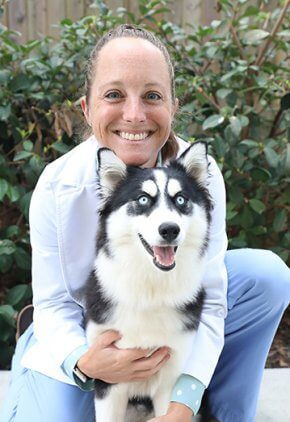 Dr. Jennifer Stafford is board certified in veterinary internal medicine and board certified in veterinary emergency & critical care. She is hugging a Husky.