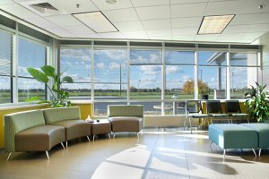A bright spacious lobby is lined with windows and seating.