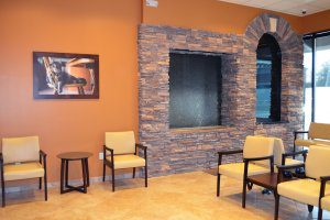 Waiting room with stone wall and tan chairs.