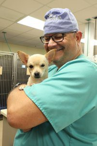 A smiling veterinary technician looks down at the dog in his arms.