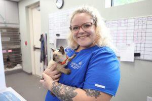 A smiling blond vet tech holds a kitten.