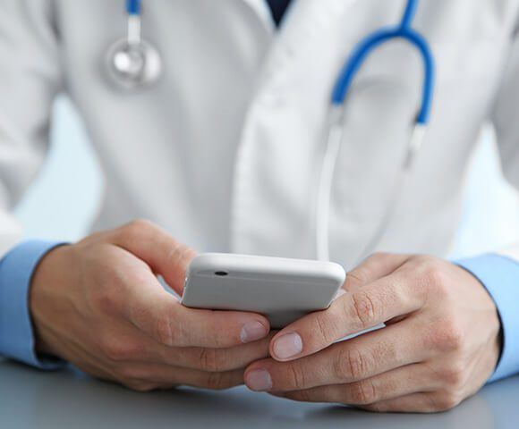 A doctor wearing a white coat checks his smart phone.