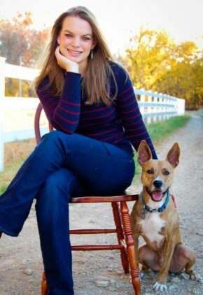 Dr. Mary Ellen Matthews is an emergency medicine veterinarian. She is sitting on a chair next to a brown dog.