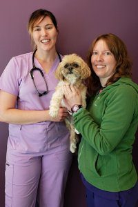 Two veterinarians stand while holding a small dog.