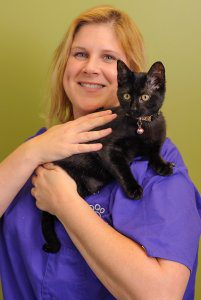 A smiling blond woman holds a black cat.