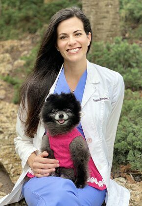 Dr. Sagan Woolery is an emergency medicine veterinarian. She is holding a black Pomeranian wearing a pink sweater.