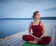 Beautiful young woman practices yoga asana Padmasana - Lotus pose on the wooden deck near the lake