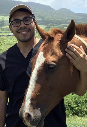 Dr. Jose Ruiz is a small animal medicine and surgery intern. He is standing next to a brown horse.