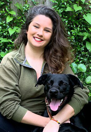 Dr. Kaitlynn Ban is a small animal medicine and surgery intern. She is hugging a black dog.