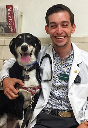 Dr. Andrew Lacqua is an intern in our surgery service. He has his arm around a black and white dog.