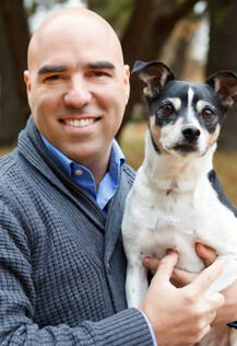 Dr. Leo Roa is a veterinarian in our emergency and critical care service. He is holding a black and white dog.
