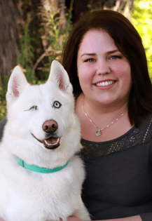 Dr. Rozemary Bal is an emergency medicine veterinarian. She is sitting next to a white dog.